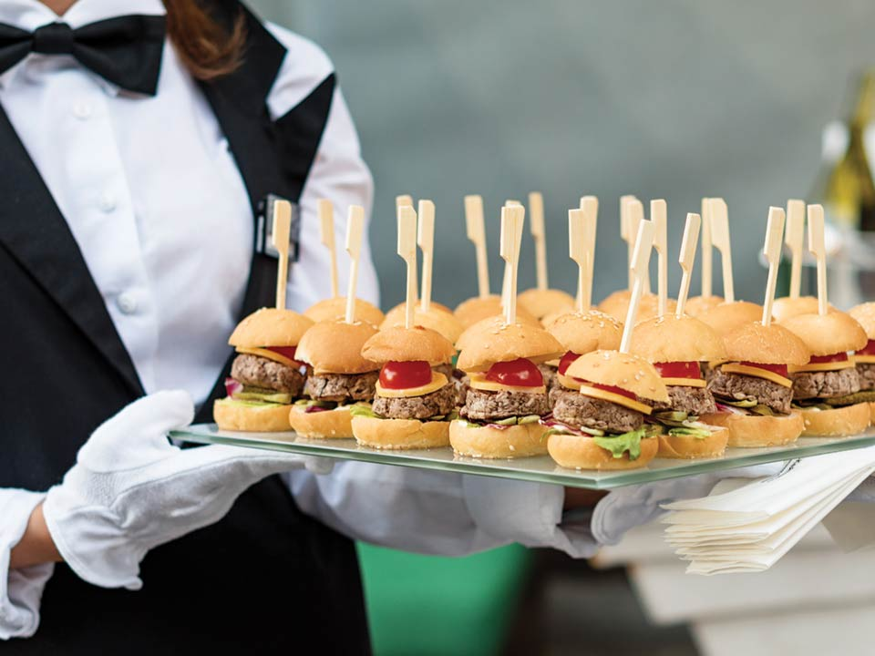 A catering waitress carrying sliders