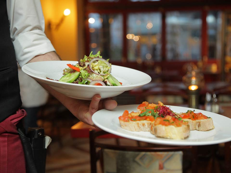 Article on Chefs. Photo: A waiter brings food to a table