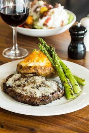 Steak, baked potato, and asparagus with a salad at Burtons Grill Mount Pleasant