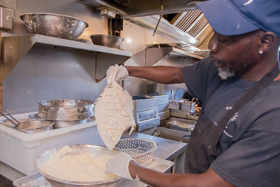 A cook prepares hand-breaded flounder at Hyman's Seafood