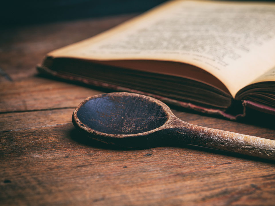 old cookbook and a well-worn wooden spoon