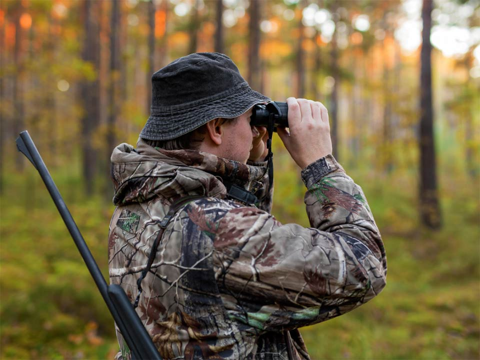 A hunter unsing a pair of binoculars to scout out a location