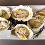 Wood-grilled oysters topped with parmesan butter.