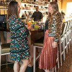 From left, Angela Holbert and Lexi Dowd share a laugh at the bar while modeling clothes from Tres Carmen.