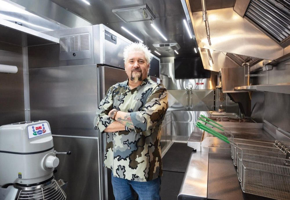 Guy Fieri in the kitchen with his arms crossed.